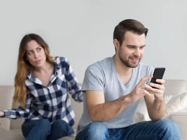 man texting next to woman